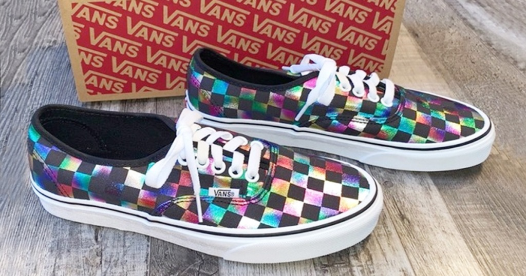 black and rainbow checkerboard print sneakers next to vans shoe box