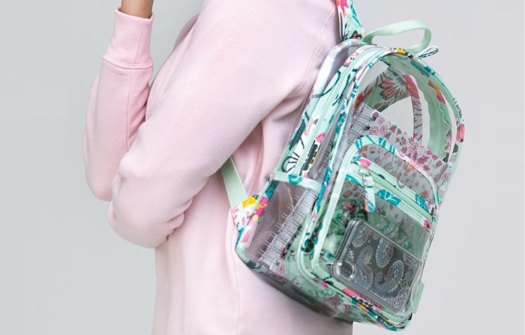 woman in pink sweater with clear and green floral clear backpack