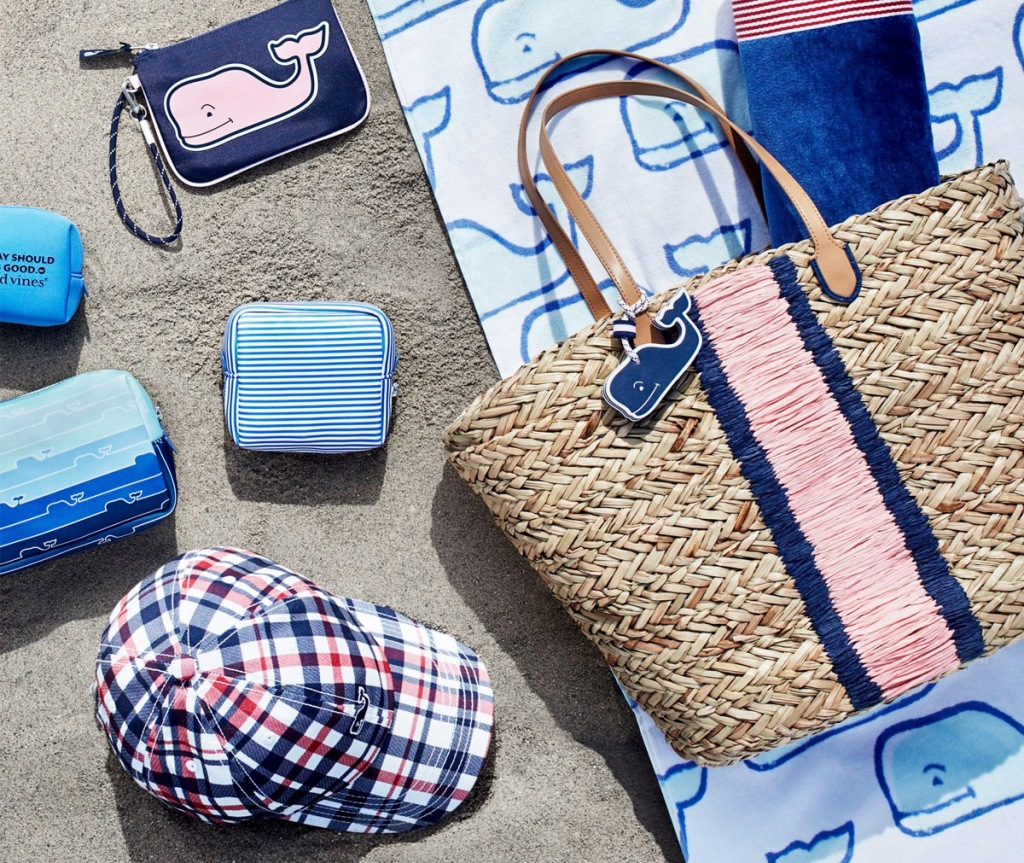 beach tote, towel, and accessories printed with vineyard vines whale all sitting on beach sand