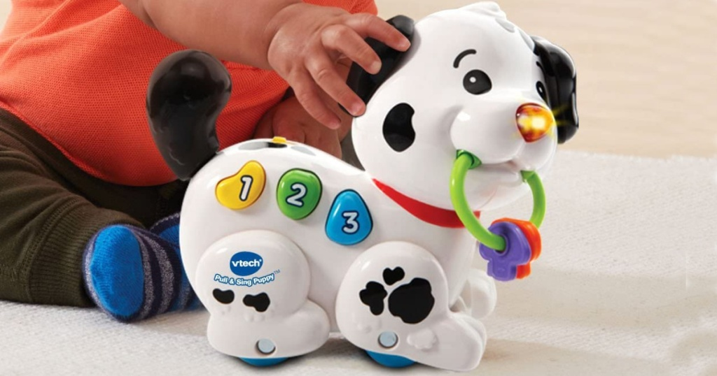 baby sitting on the floor playing with Vtech Pull and Sing Puppy toy