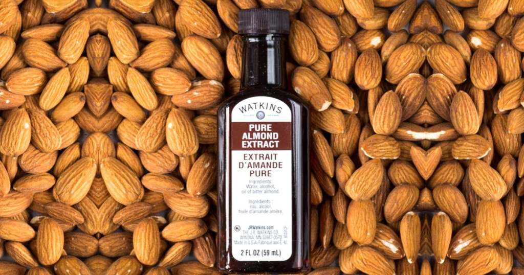 bottle of Watkins Pure Almond Extract on a bed of almonds