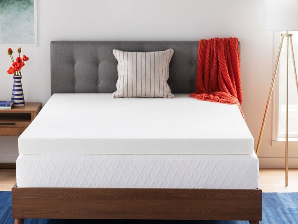 bed with mattress topper in room with furniture and bedding
