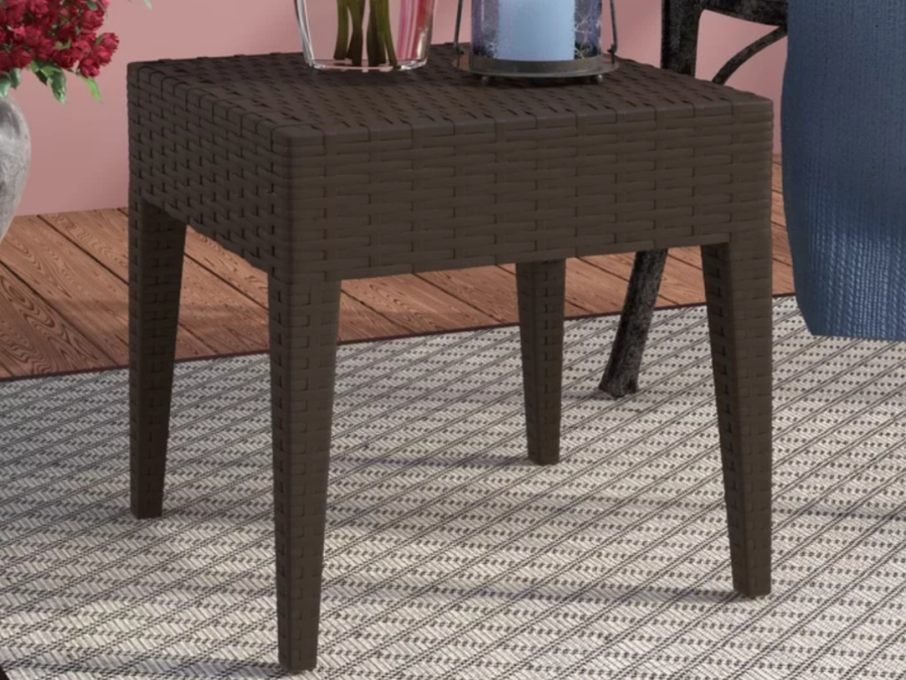 dark brown outdoor side table with items on top