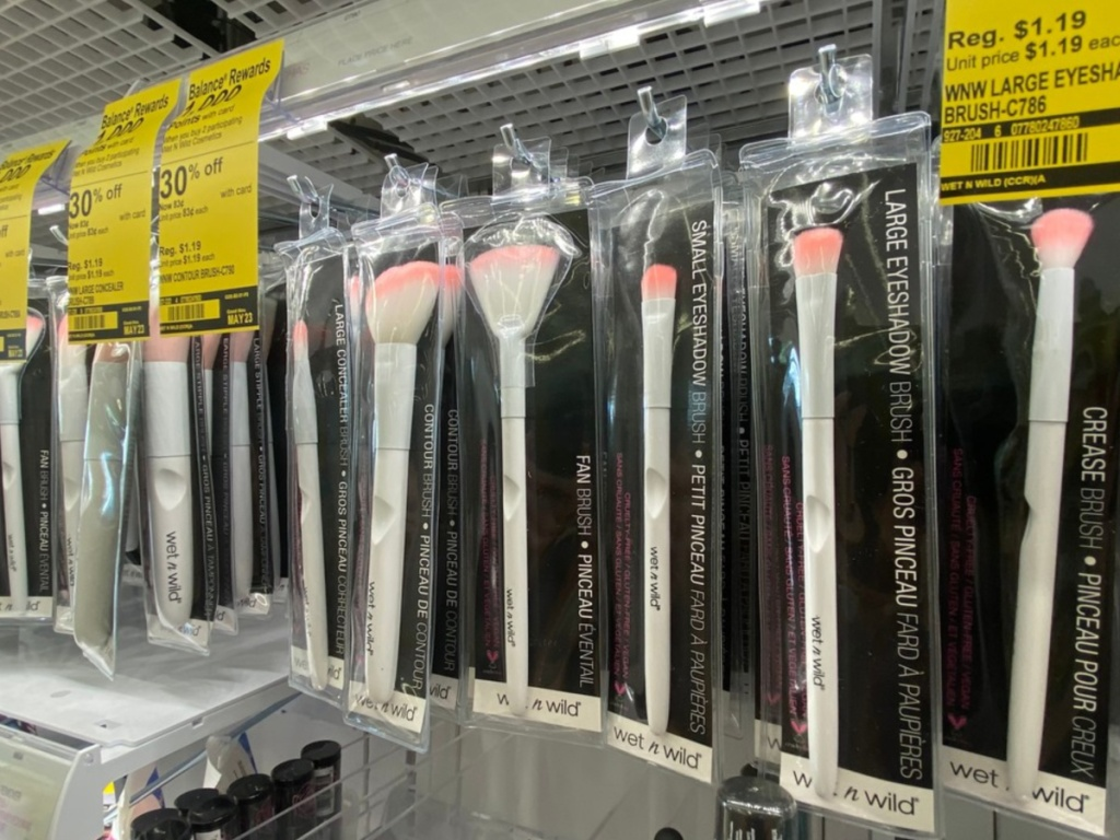 row of white and pink makeup brushes in packaging hanging in store