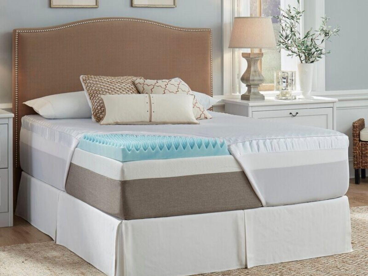 exposed mattress and mattress topper on bed in room with furniture and lamp