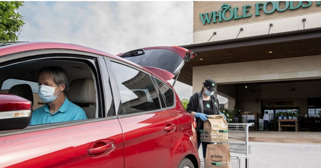 High risk man in car w/ face mask picking up groceries at Whole Foods