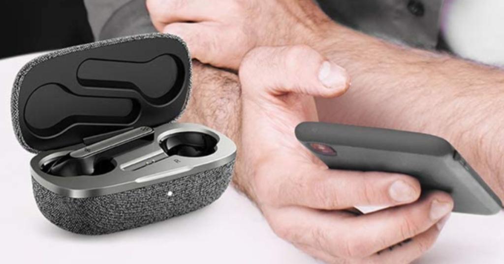grey wireless earbuds sitting inside a grey charging case next to a hand holding a smartphone