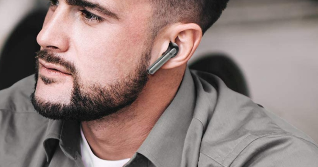 man with a beard wearing a pair of grey wireless earbuds