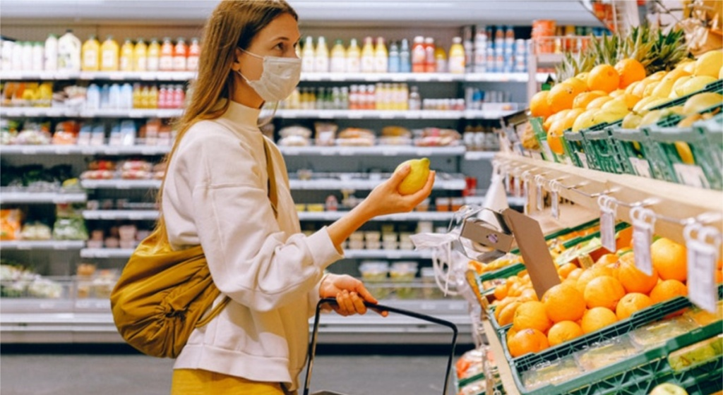 woman in face mask grabbing produce in store