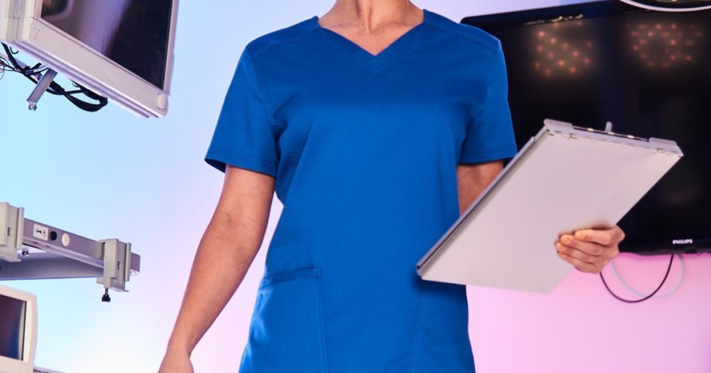 Woman wearing blue scrub top holding a clipboard in her hands