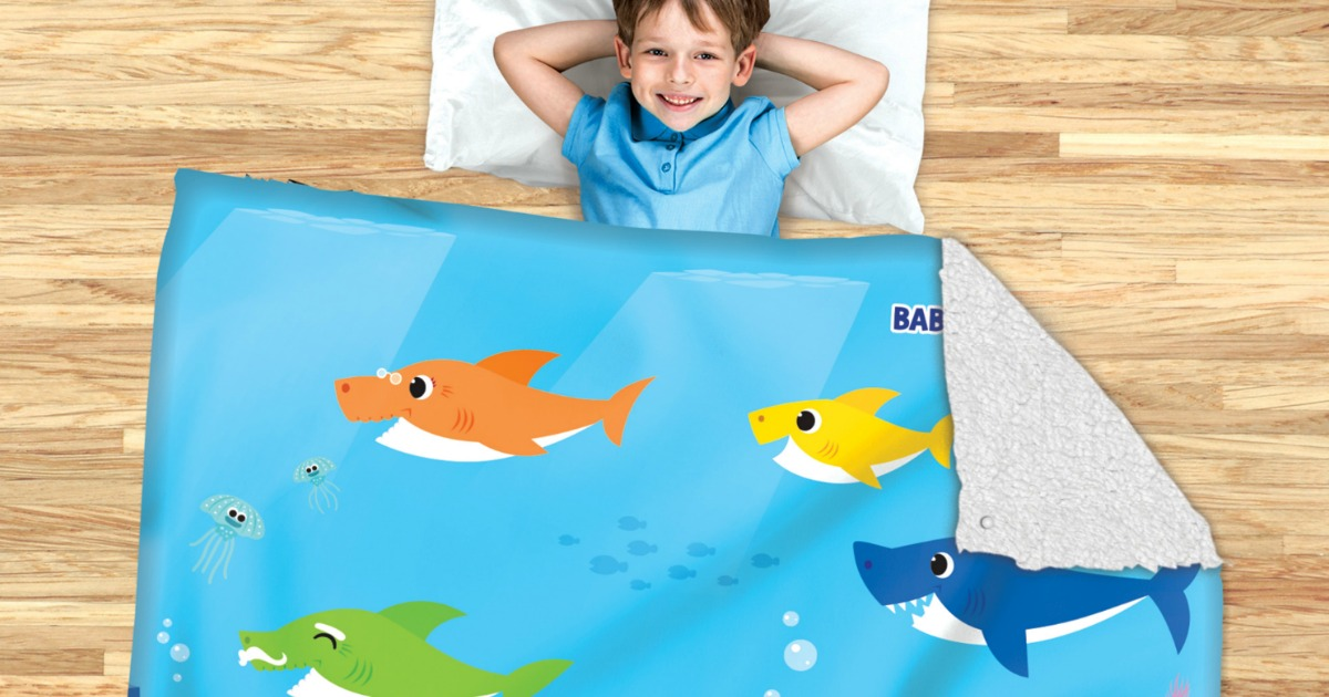 child with head on pillow laying under baby shark blanket