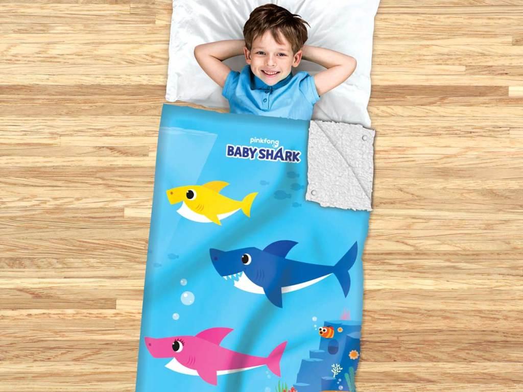 little boy sleeping in a baby shark sleeping bag