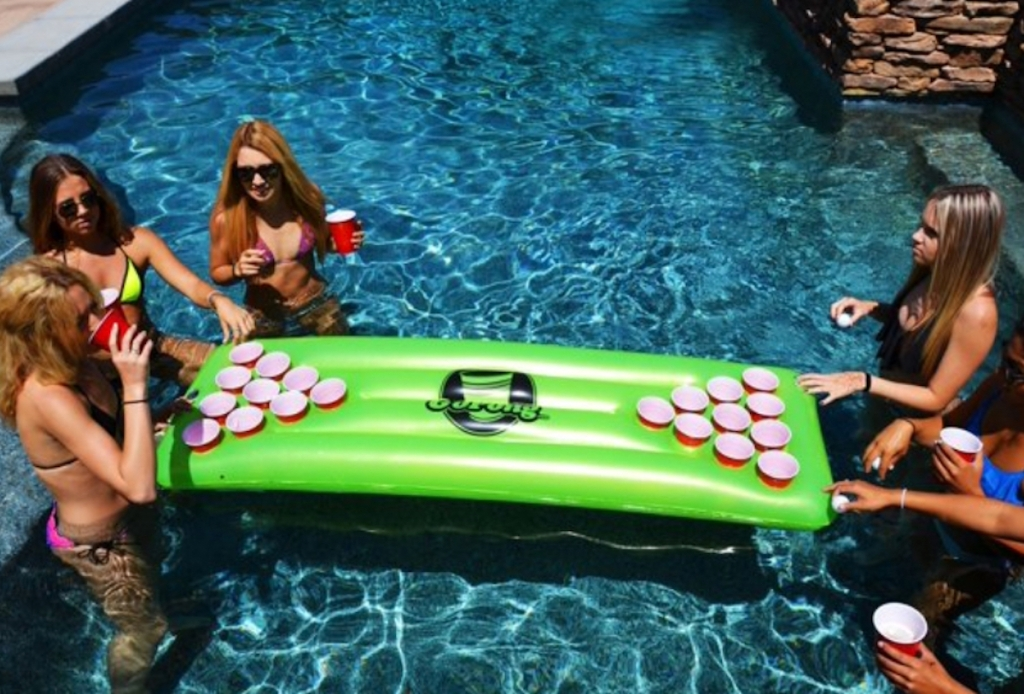 people in pool surrounding green pool float with cups