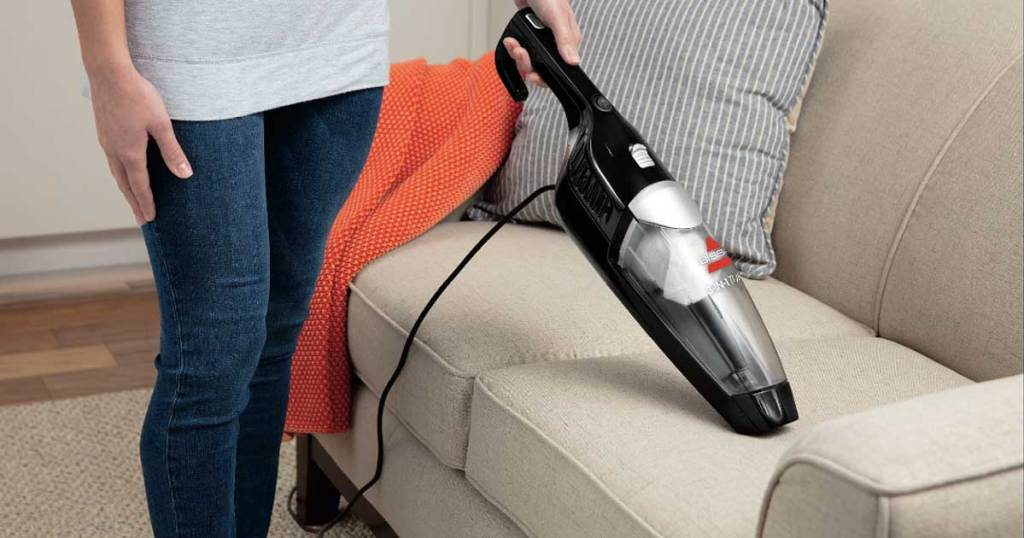 woman holding a bissell hand vacuum in her hand on the couch