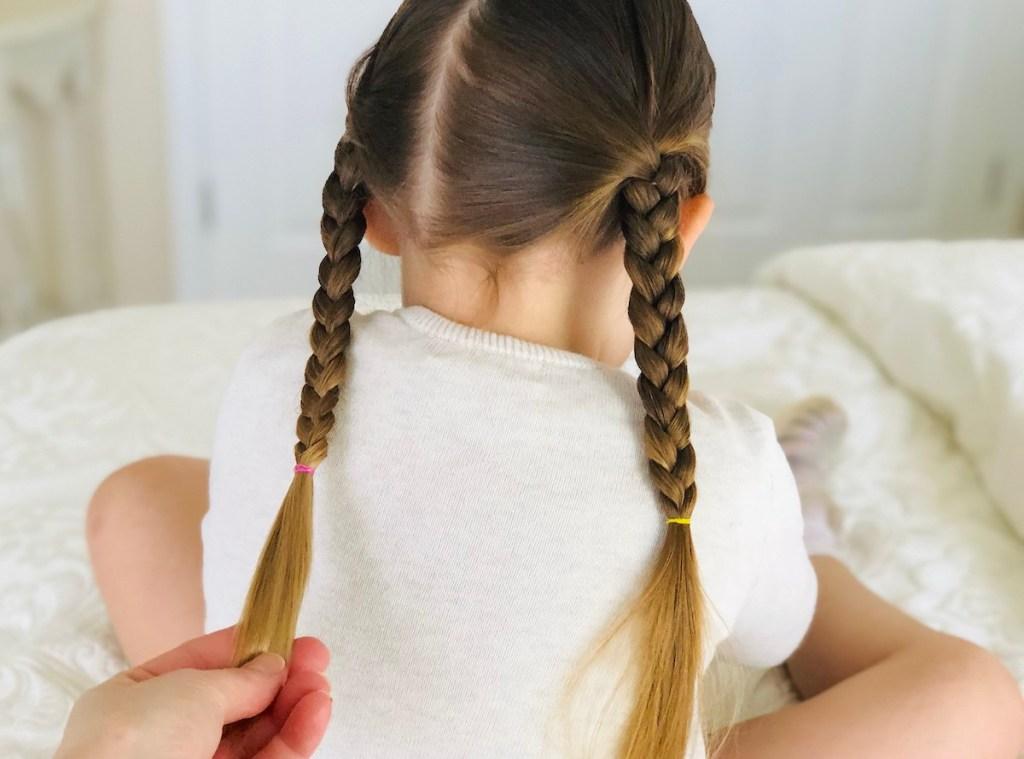 hand holding a braid on girls head