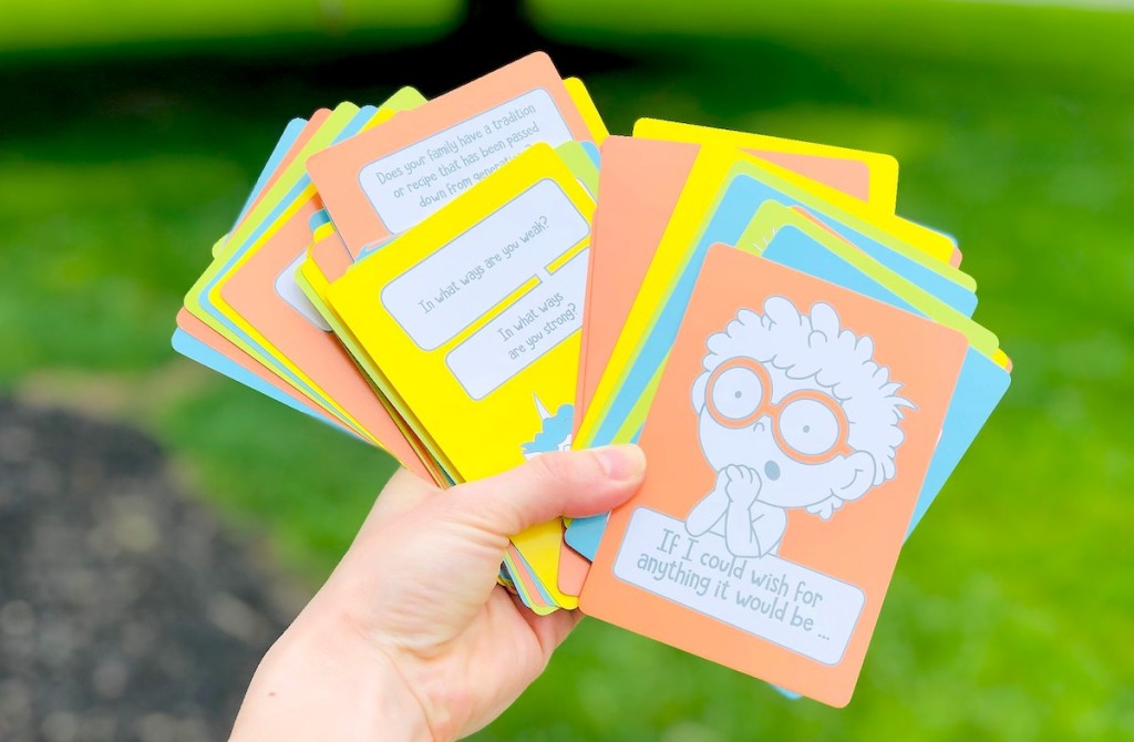 hand holding a colorful deck of conversation cards