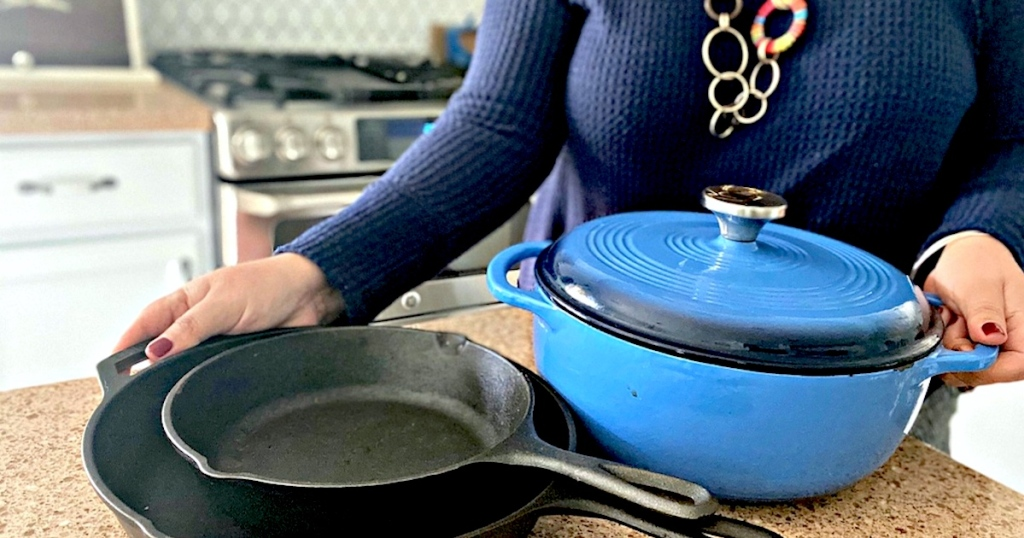 woman holding black and blue cast iron pots and pans