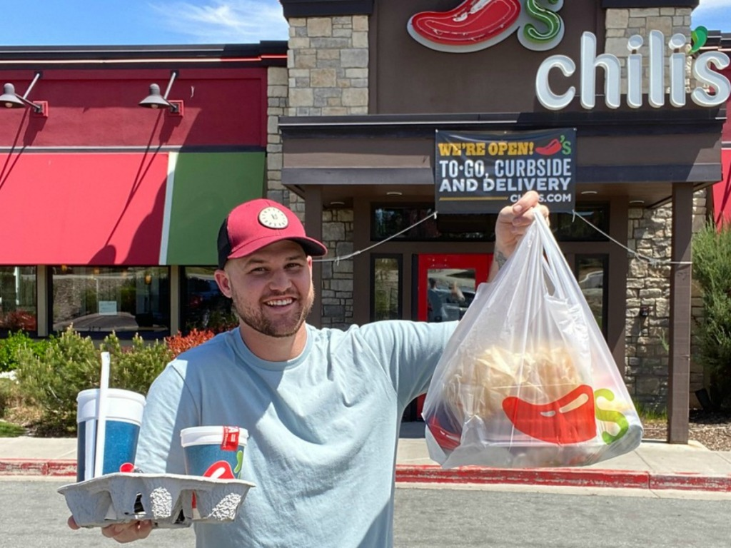 man holding up bag of food and drinks in front of restaurant