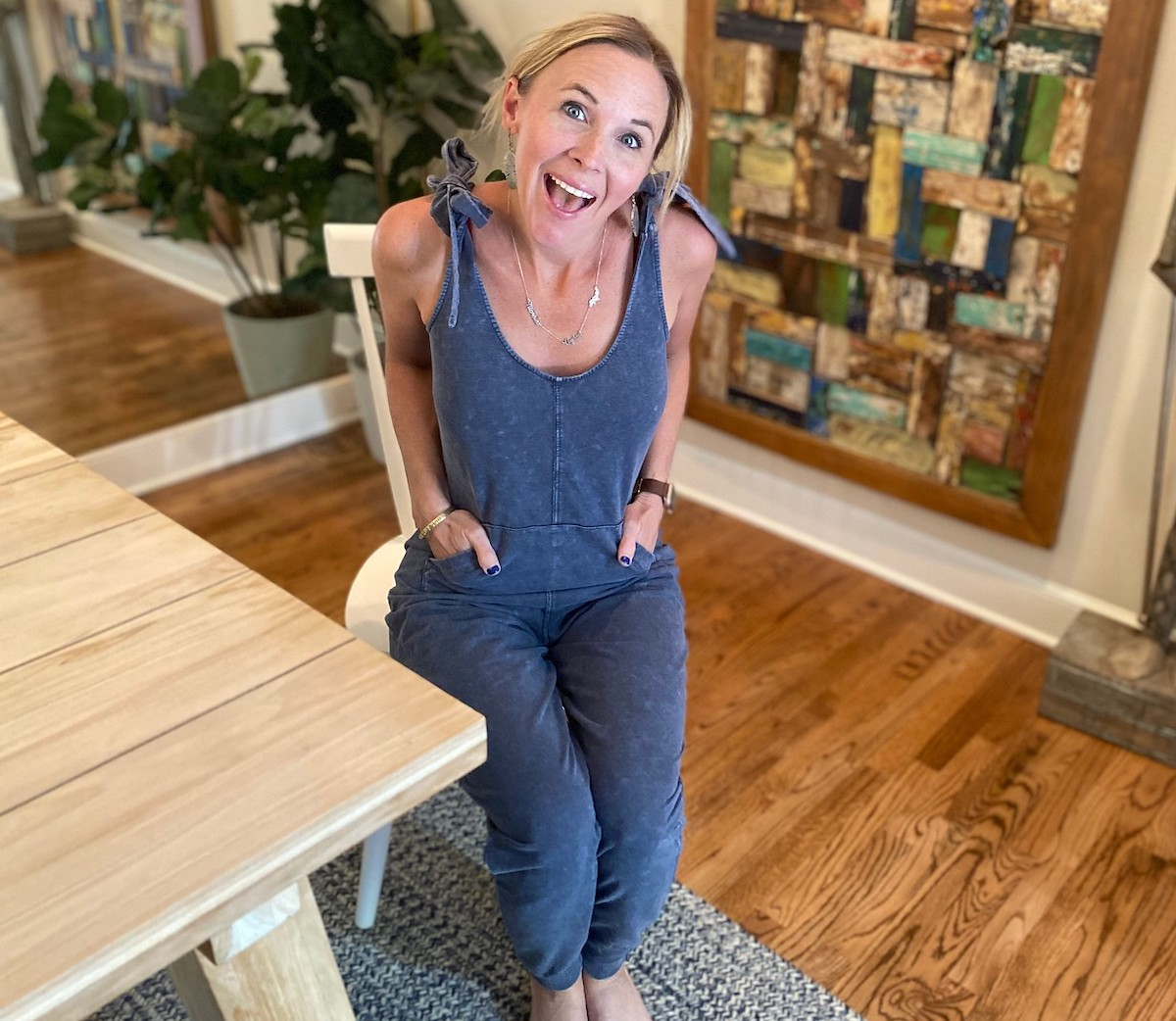 woman wearing blue jumpsuit sitting in white dining room chair looking excited