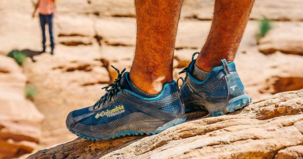 man wearing Columbia shoes on mountain top