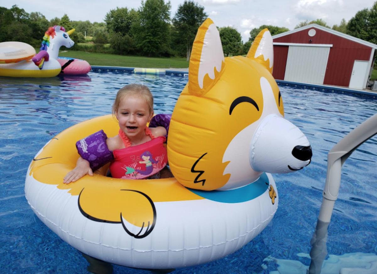 toddler girl sitting in dog pool float