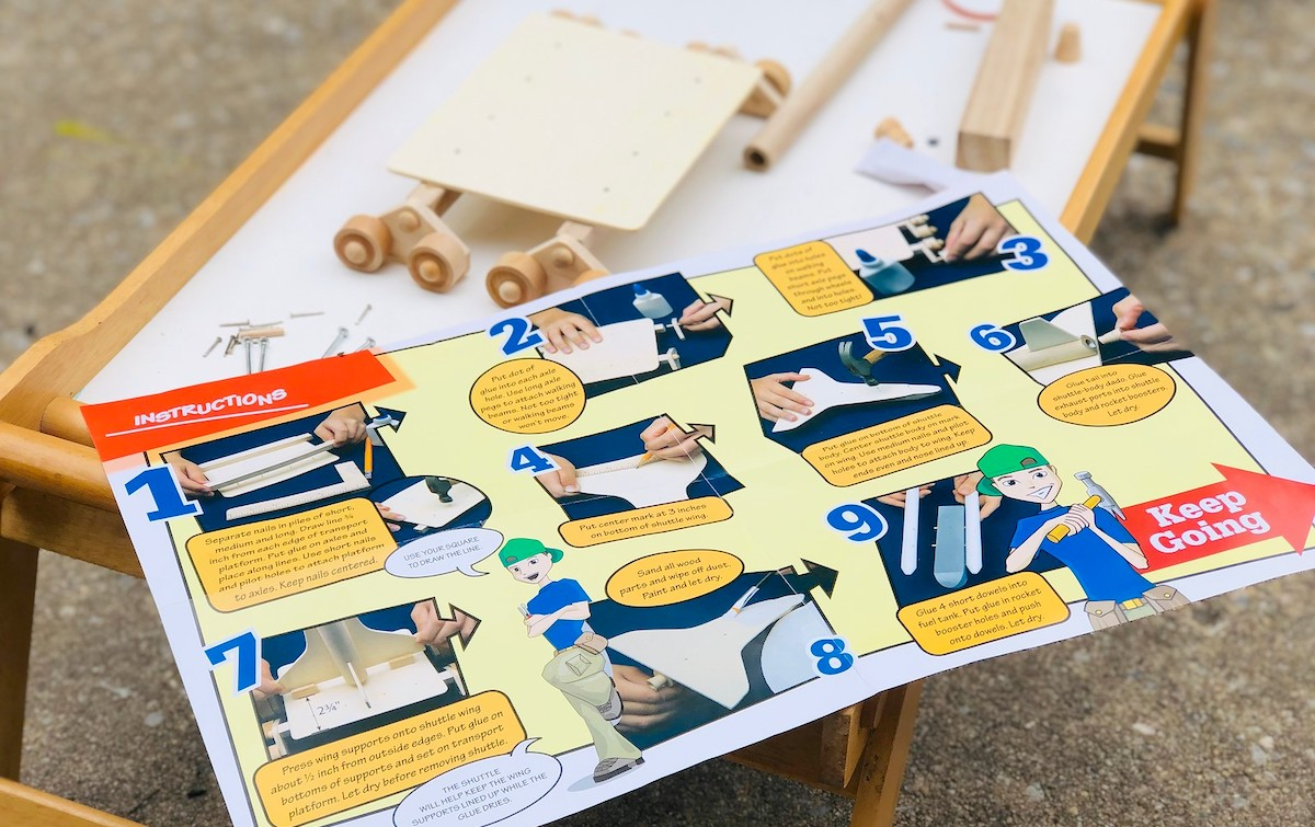 colorful building directions laying on tray table with wood craft project