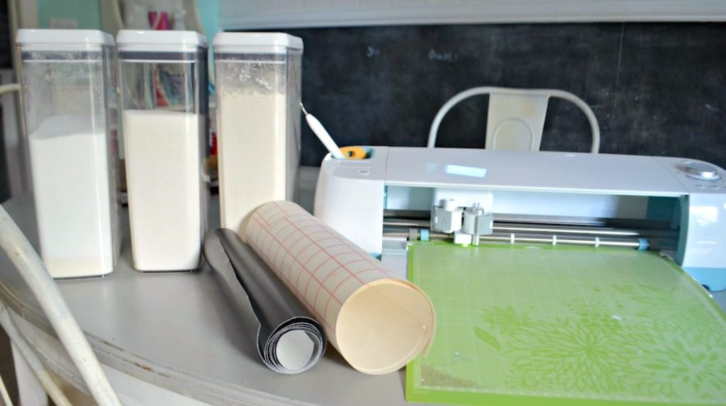 containers with dry baking food and rolls of adhesive sticker sitting next to cricut maching