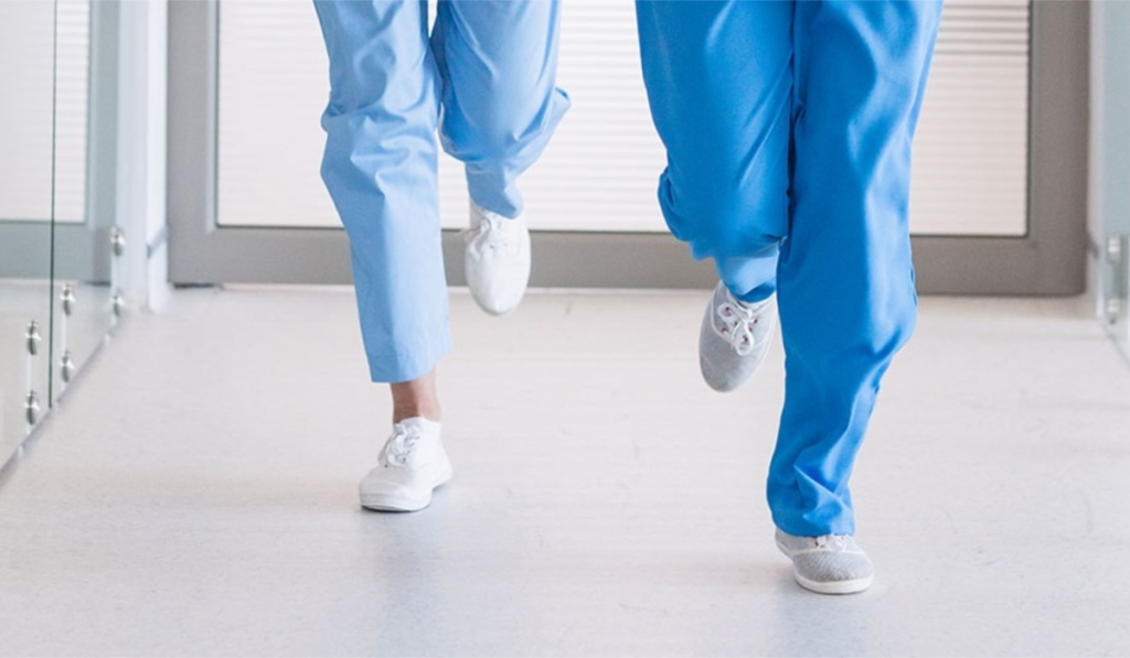 foot level view of medical workers wearing tennis shoes and running