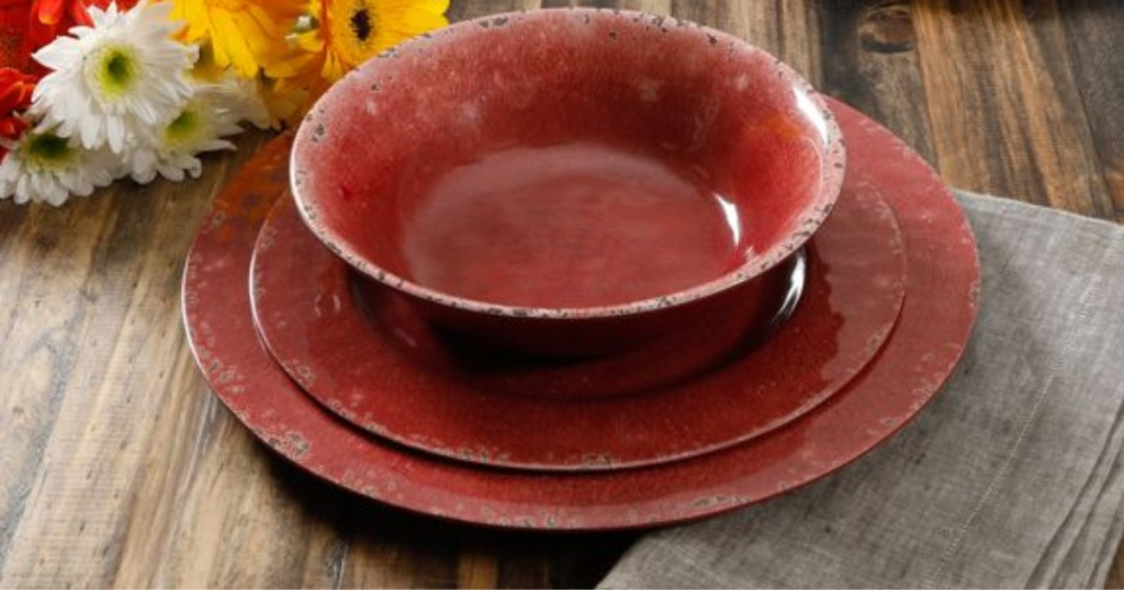 red dinnerware set on table with flower