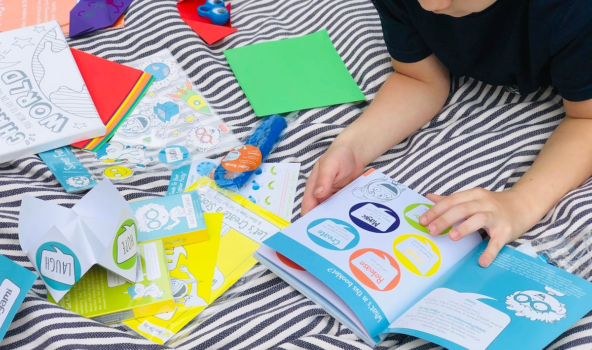 boy reading booklet with other various activities and games on stripe blanket