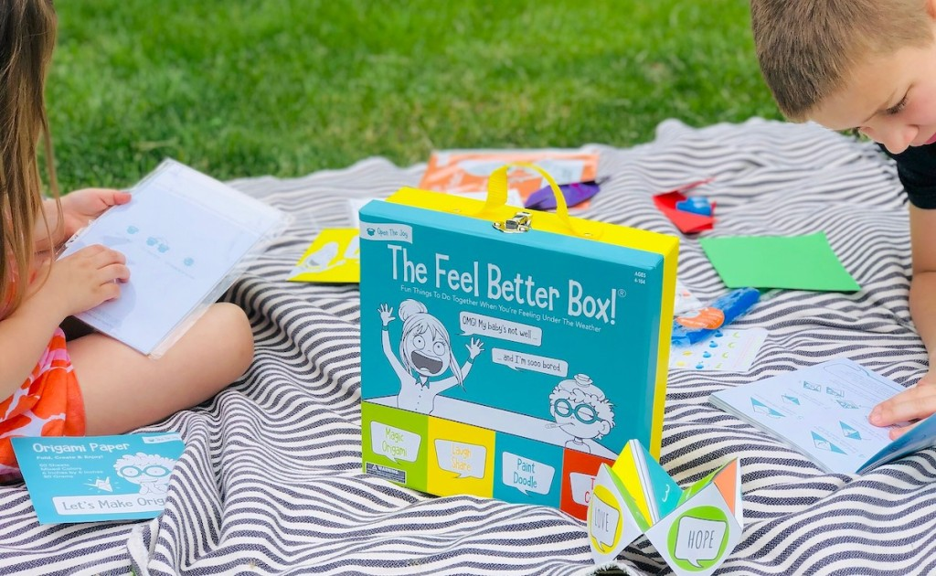 blanket in grass with feel better box and activities