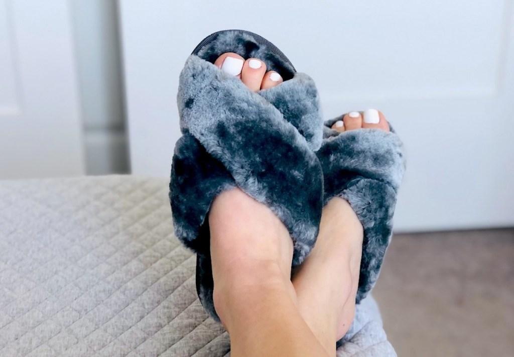 feet wearing dark gray fuzzy slippers with white toenail polish