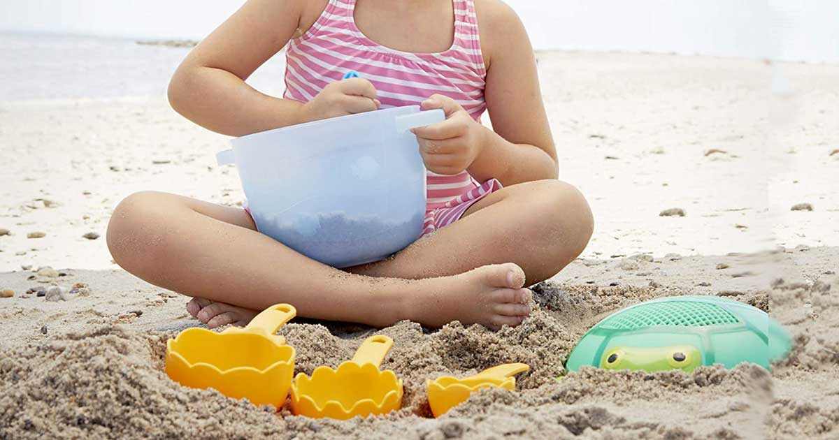 girl on the beach playing with Melissa & Doug Seaside Sidekicks Sand Baking Set