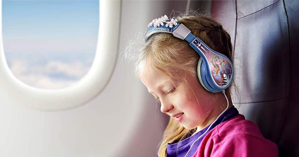 girl using eKids KIDdesigns Frozen Cool Tunes Headphones on airplane