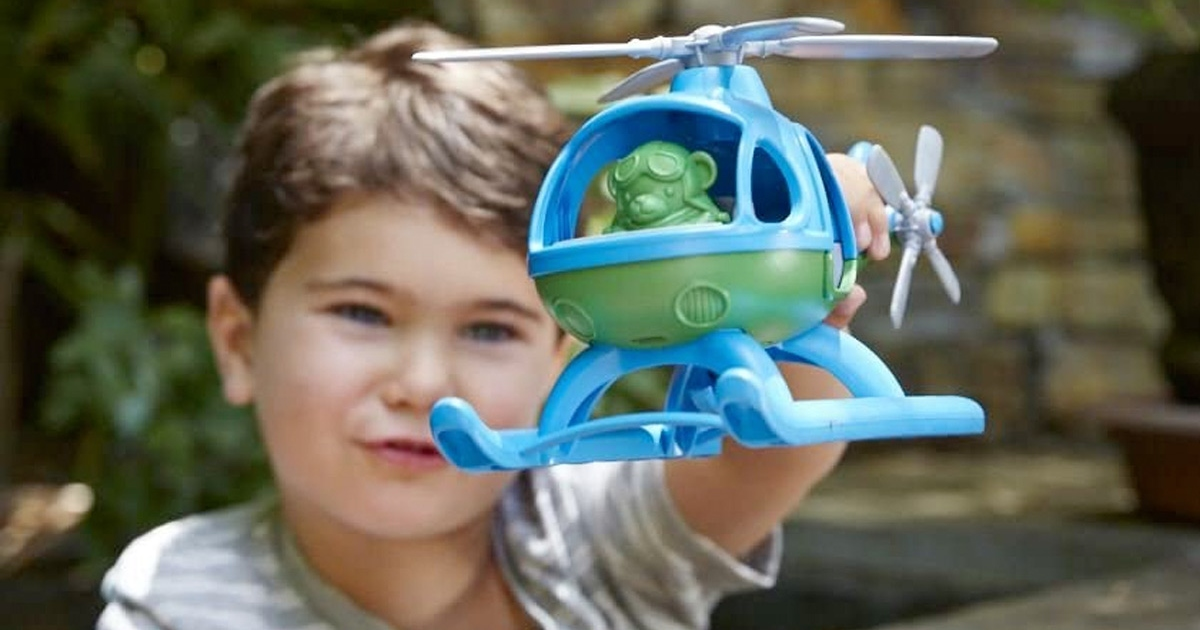 young boy playing with toy helicopter