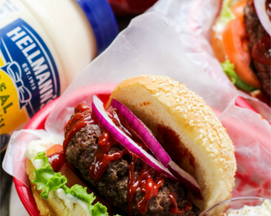 hellmans mayo with burger and other condiments on it