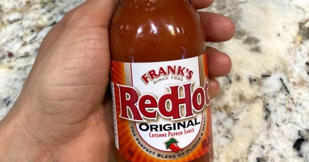 hand holding bottle of hot sauce