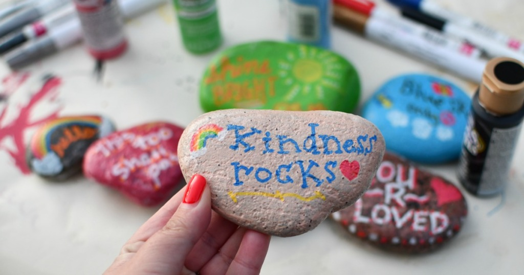 holding a painted kindness rock