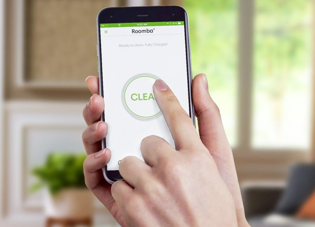 person holding smartphone with iRobot app to begin Roomba cleaning cycle