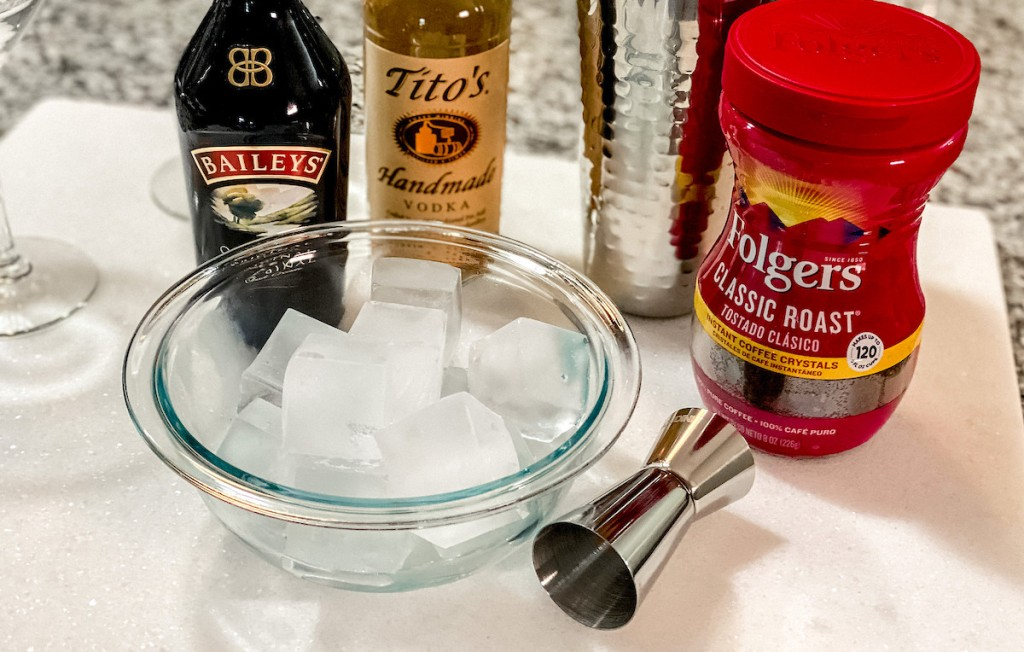clear bowl of ice cubes with baileys titos and folgers in background