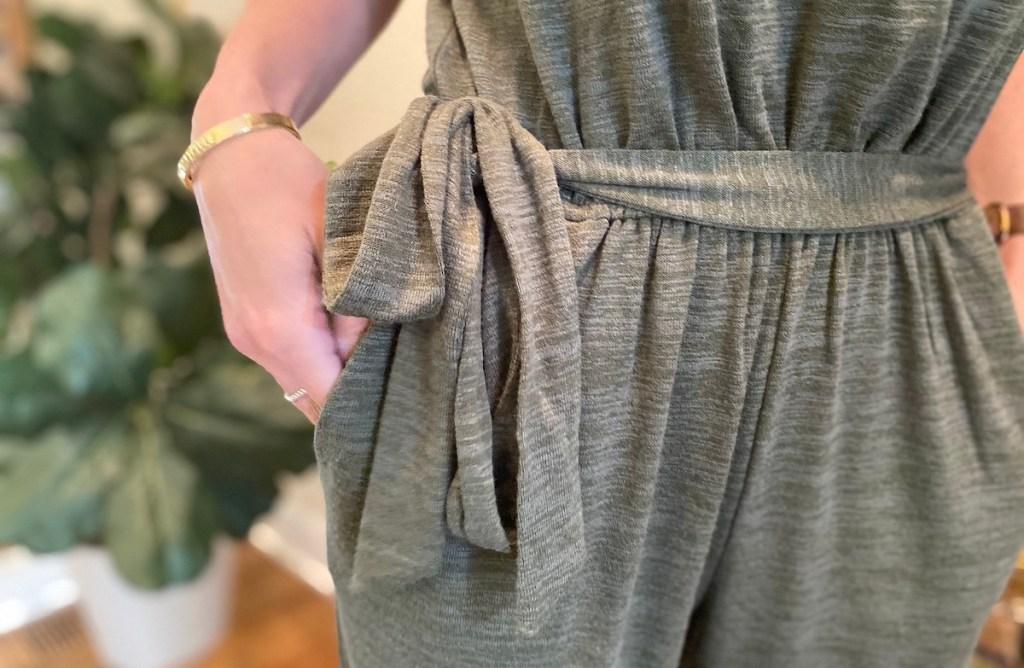 hand going in romper pocket with tie belt at waist
