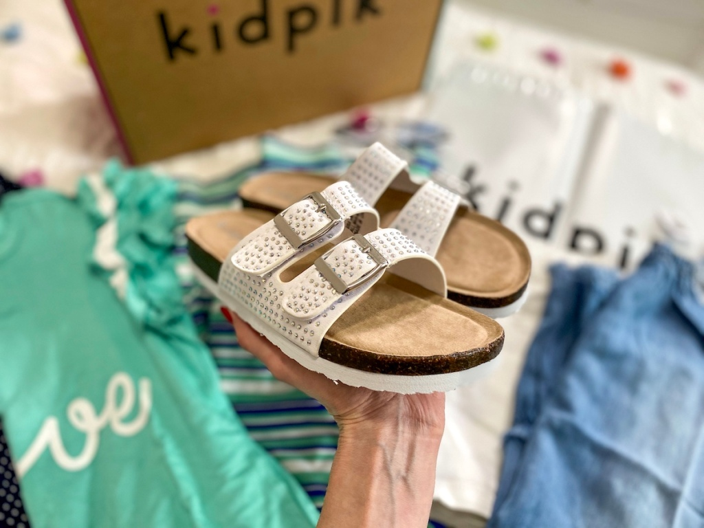 hand holding white pair of kids sandals behind kidpik clothing and box