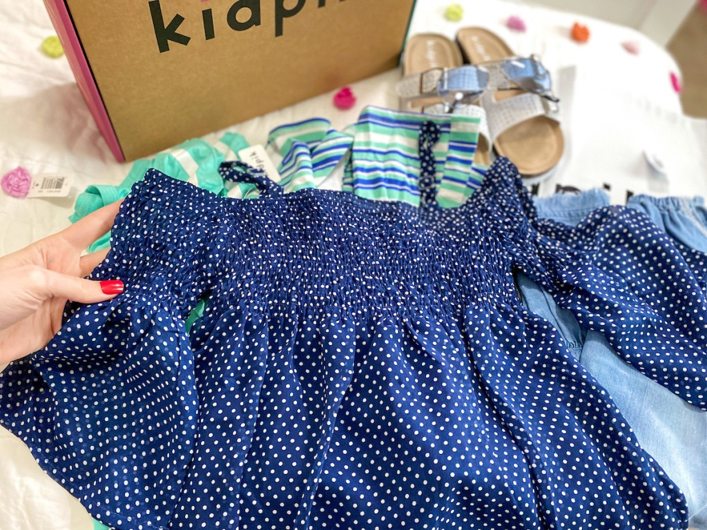 dark blue kids top with white polka dots with kidpik box behind it