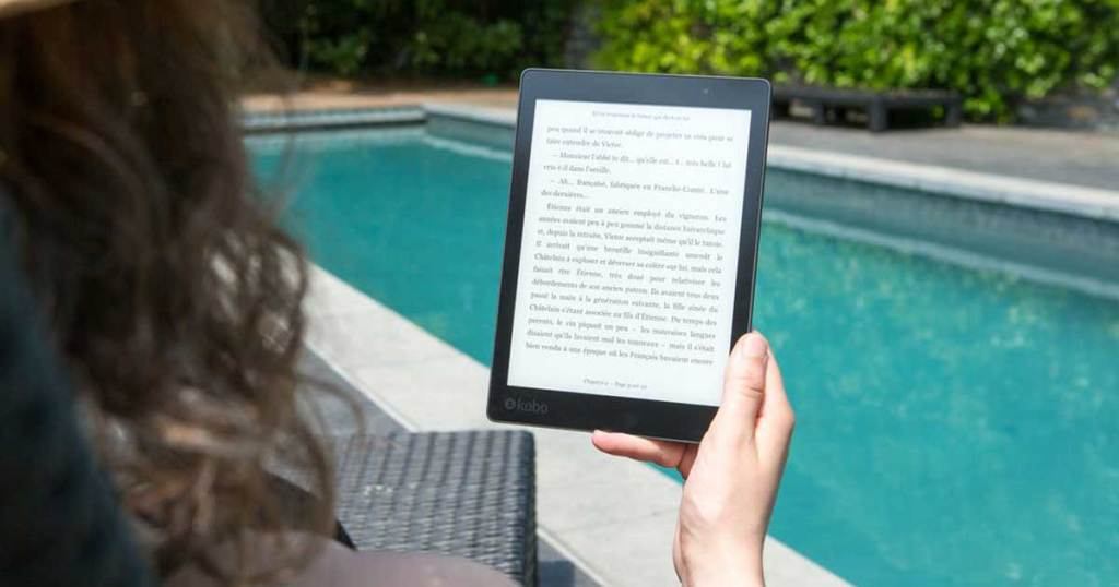 woman looking at kindle by the pool