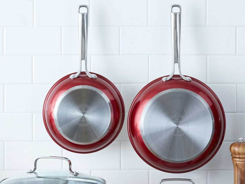 two red skillets handing on a kitchen subway tiled wall