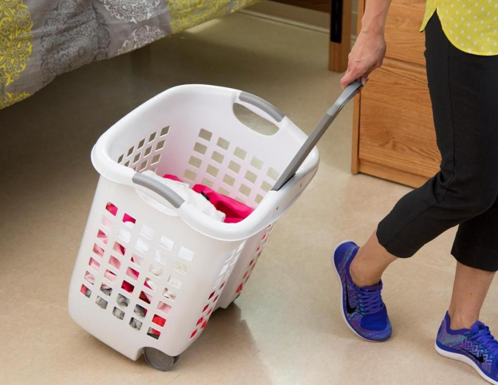 person pulling white laundry basket with wheels
