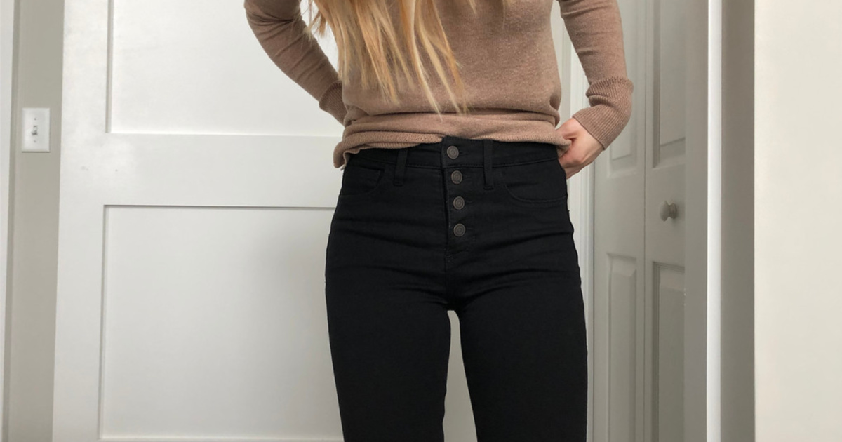 woman wearing brown sweater and black jeans with 4 buttons in front