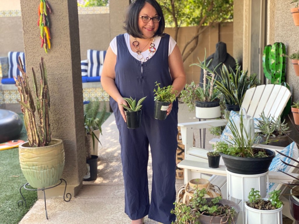 woman wearing romper holding two small green plants outside