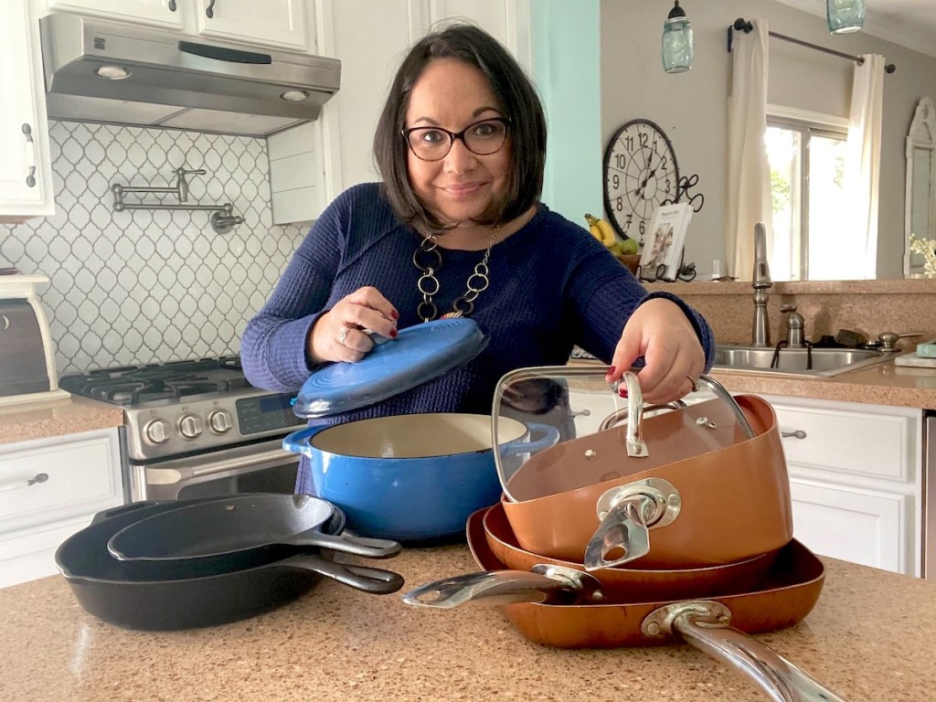woman showing off various styles and colors of pots and pans