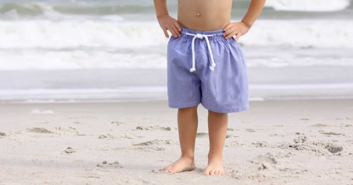 little boy standing on the ocean